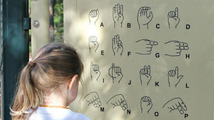 Niña ante el abecedario de signos (Foto: SaraSmo | Flickr)