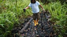 Ermel Chávez muestra el crudo de una piscina abierta en el pozo Aguarico 4 (Ecuador). / Miriam Gartor.