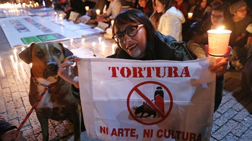 Una mujer sostiene un cartel durante una jornada de protesta contra las corridas de toros, en la Plaza de Toros La Santamaría de Bogotá (Colombia).