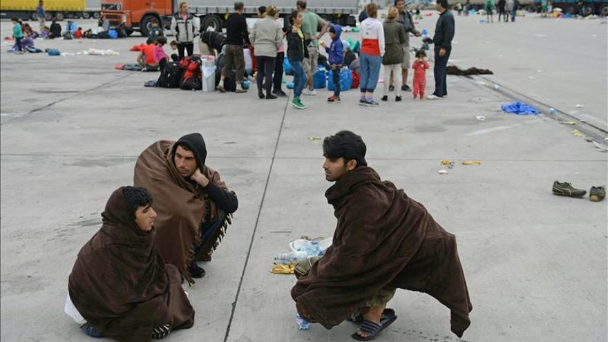 Un grupo de refugiados sirios tras su llegada de Hungría descansan en la localidad austríaca de Nickelsdorf. / EFE.