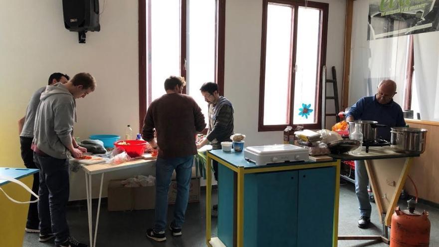 Hombres preparan la comida en el Espacio Vecinal de Arganzuela