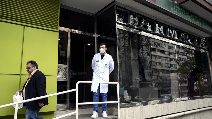 Un farmacéutico protegido con mascarilla en la puerta de una Farmacia | ÓSCAR CAÑAS