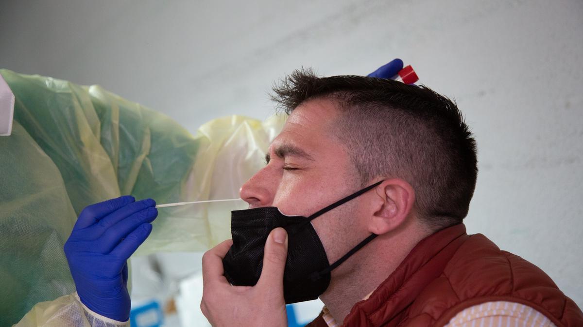 Una sanitaria realiza un test de antígenos o una PCR a un hombre