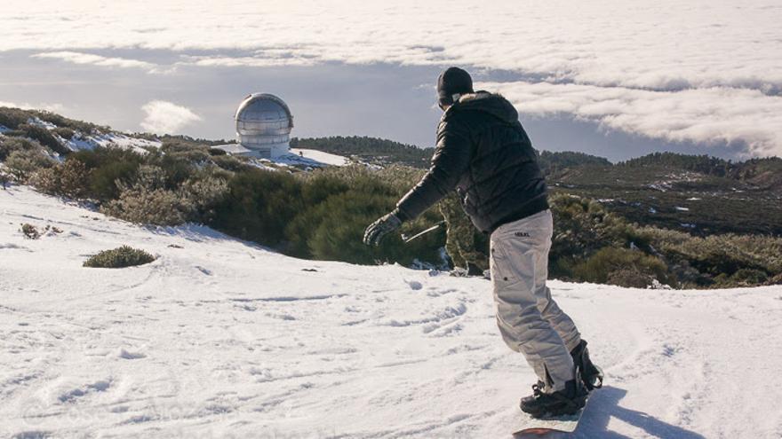 Un 'snowboarder', este viernes, en El Roque Los Muchachos, con el Gran Telescopio de Canarias al fondo. Foto: JOSÉ F. AROZENA.