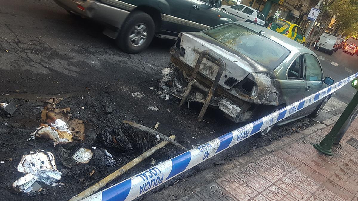 Un vehículo afectado por el incendio de unos contenedores.