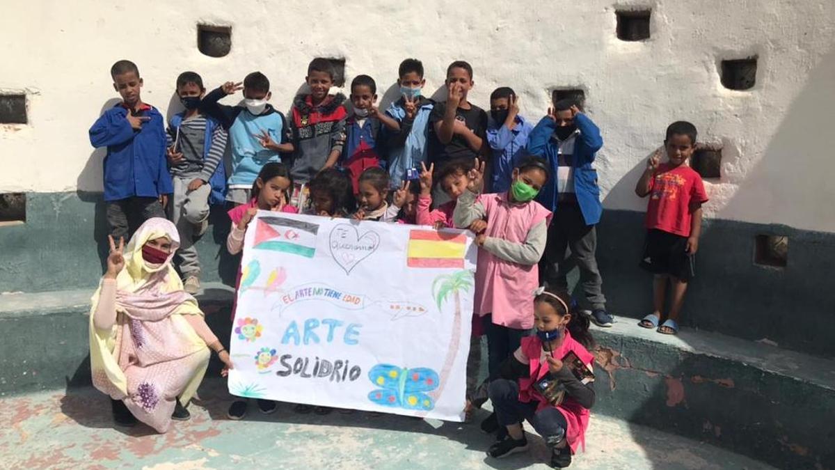 Niños saharauis del campamento de Tinduf con un dibujo de arte solidario.