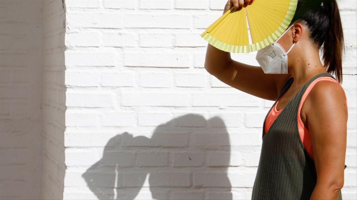 Imagen de archivo de una mujer caminando con un abanico para protegerse del sol y el calor