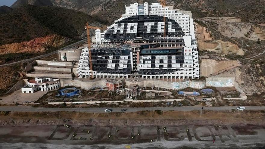 Una veintena de activistas de Greenpeace escriben 'Demolición' frente al hotel del Algarrobico