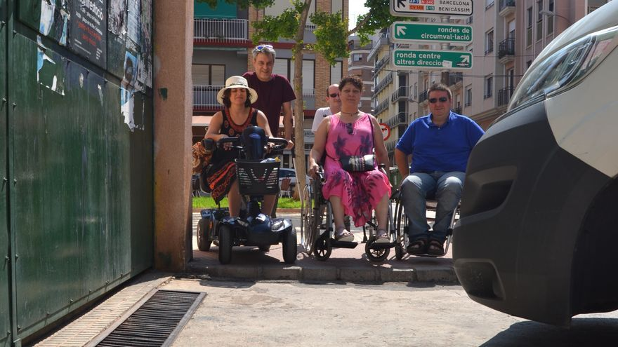 """Miembros de la Plataforma Castelló Vida Independiente posan junto a un escalón y una acera invadida por coches, dos de las """"trampas"""" habituales en su movilidad diaria por la ciudad."""