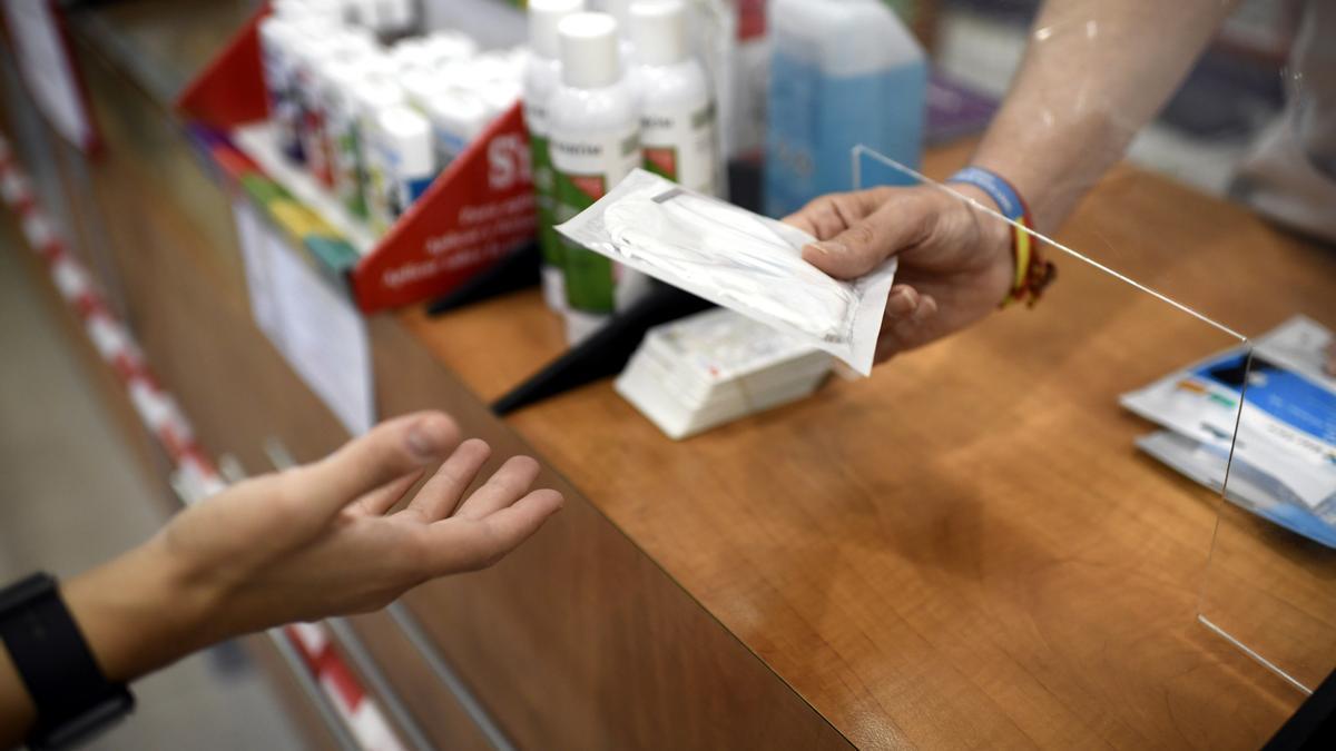 Un farmacéutico entrega a un cliente una mascarilla