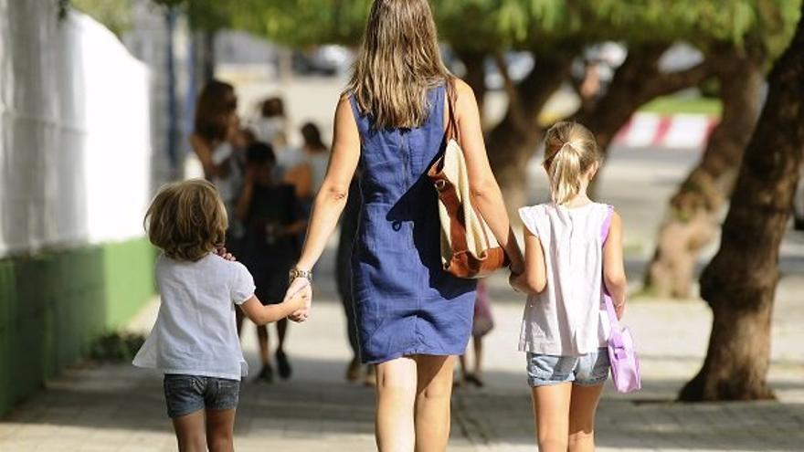 Una madre pasea junto a sus dos hijas