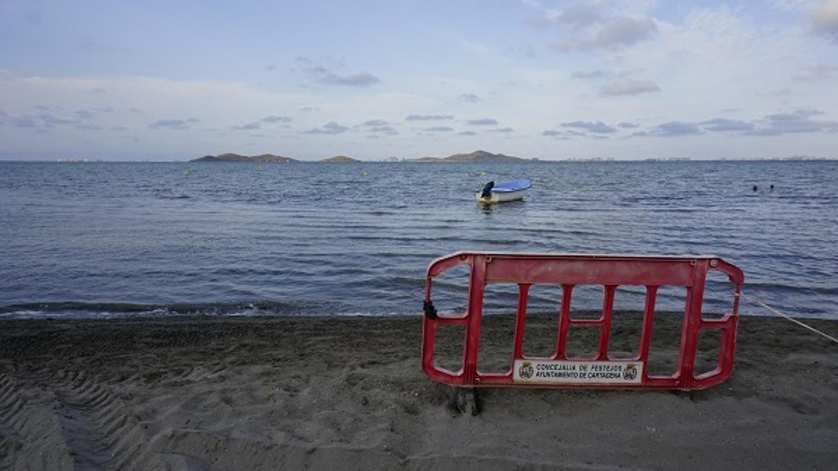 Una de las playas de Los Urrutias, en el Mar Menor, con una valla de protección del Ayuntamiento de Cartagena