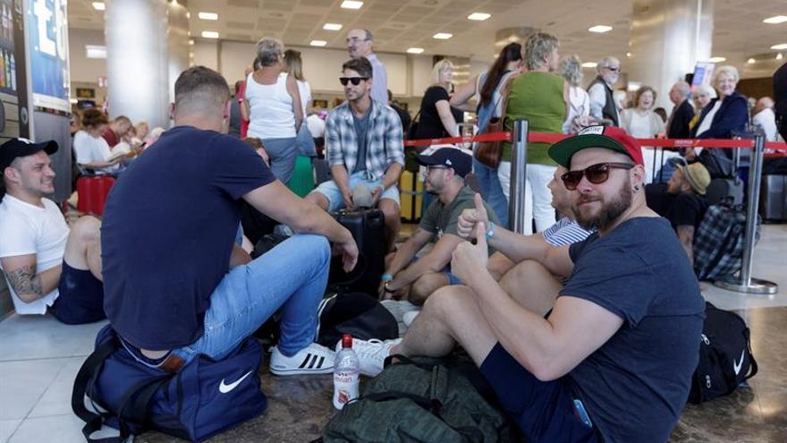 Varios pasajeros de Thomas Cook esperan para facturar en el aeropuerto Tenerife Sur para ser repatriados a Reino Unido