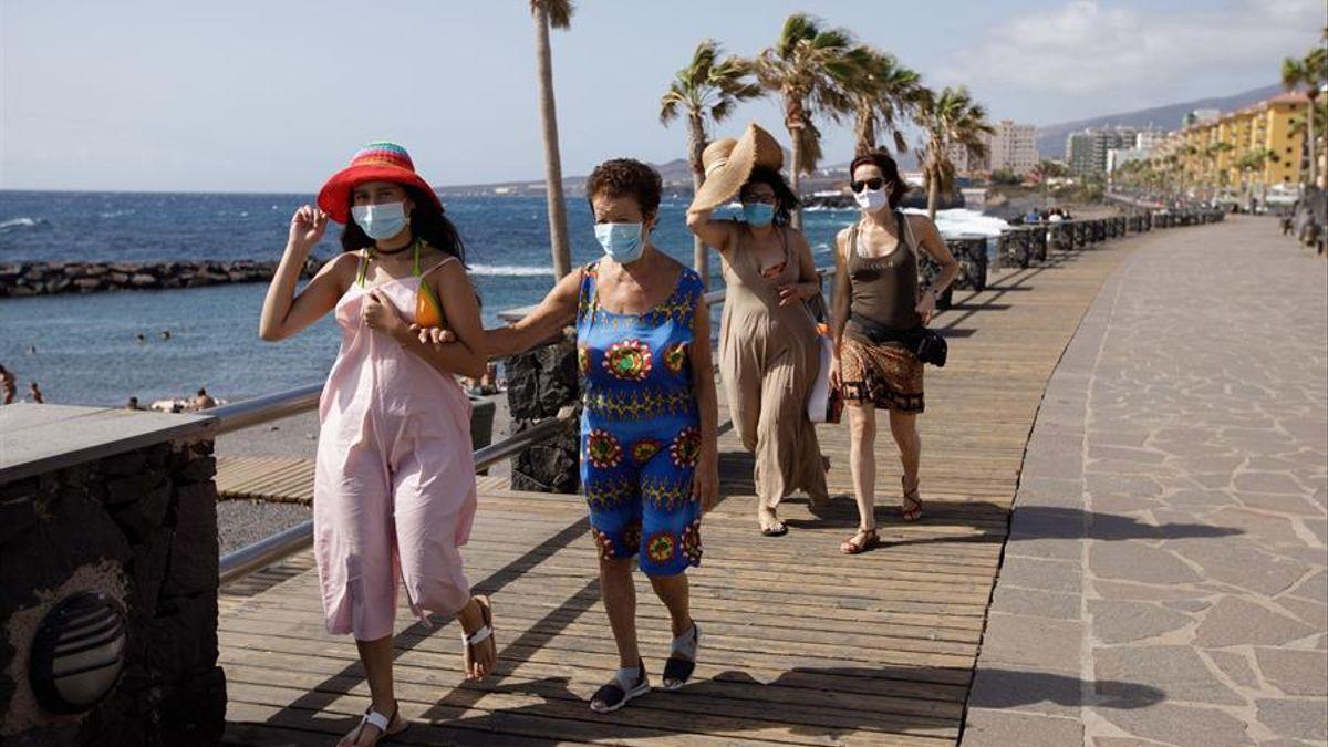 Un turistas caminan por un paseo cercano a la playa de Las Caletillas, en el municipio de Candelaria (Tenerife)