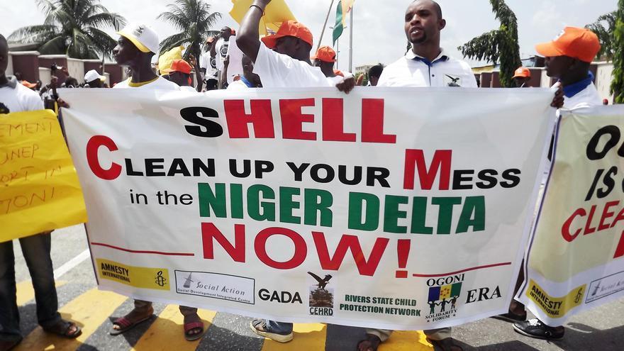 """ABRIL. """"Shell, limpia tu desorden"""": activistas de varias organizaciones se lo dejan así de claro a la compañía petrolera, a la que le exigen que """"se haga cargo, pague y limpie"""" el Delta de Niger. Una demanda civil presentada por cuatro agricultores de la región alega que los derrames de petróleo de oleoductos de Shell han destruido sus medios de vida. La demanda obligó a la empresa a comparecer ante un tribunal holandés de La Haya. #ddhhcontaminados // © Amnesty International"""