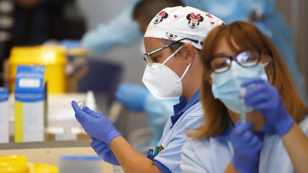 Trabajadoras sanitarias preparan dosis de la vacuna para su administración.