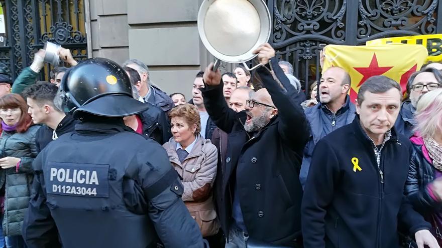 Un manifestante, con su paella frente a un mosso