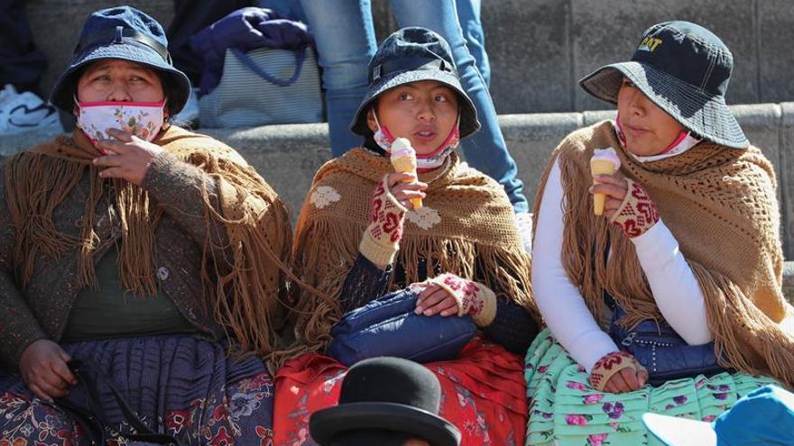 Jóvenes aimaras fueron registradas este viernes al comer helado, en La Paz (Bolivia).
