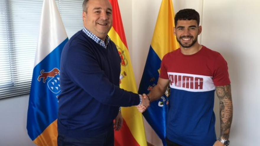El presidente de la UD Las Palmas, Miguel Ángel Ramírez y el jugador Tanausú Domínguez tras firmar la renovación. (Página oficial UD Las Palmas).