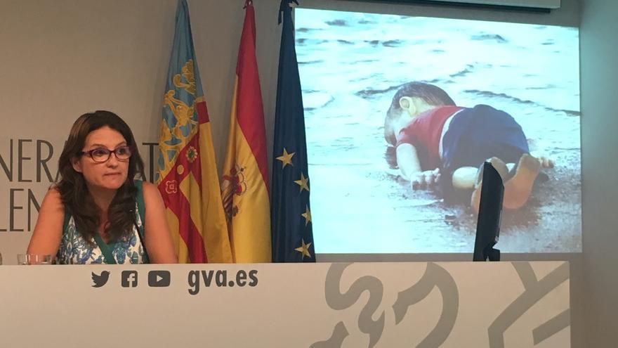 Mónica Oltra reclama la acogida a refugiados ante una foto del niño Aylan Kurdi, muerto en una playa de Turquía.