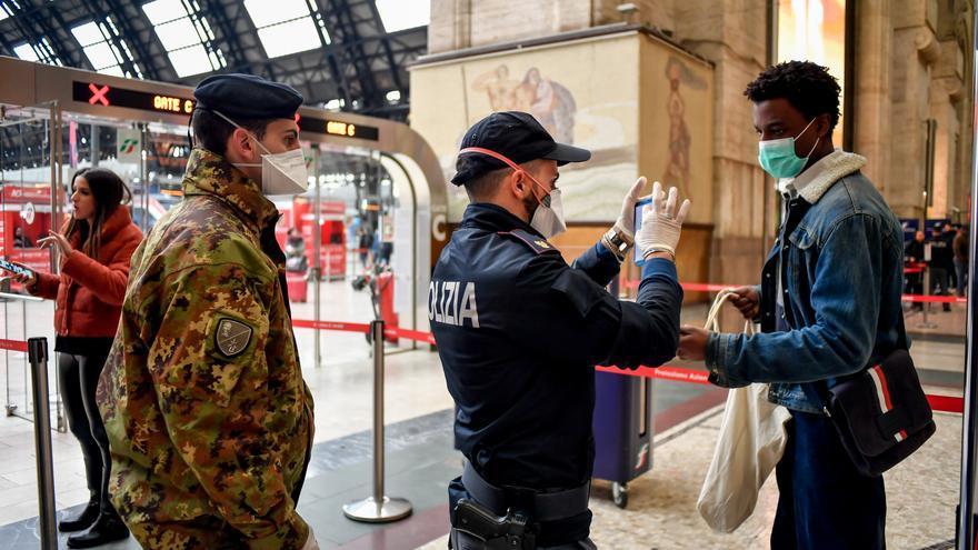 Un policía controla a un pasajero en la estación de tren de Milán.