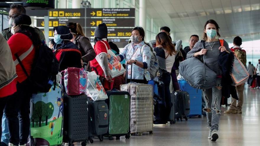 Varios viajeros transitan por el aeropuerto de Barcelona este sábado, muchos de ellos pertrechados con mascarillas, para volver a casa debido a la pandemia del coronavirus.