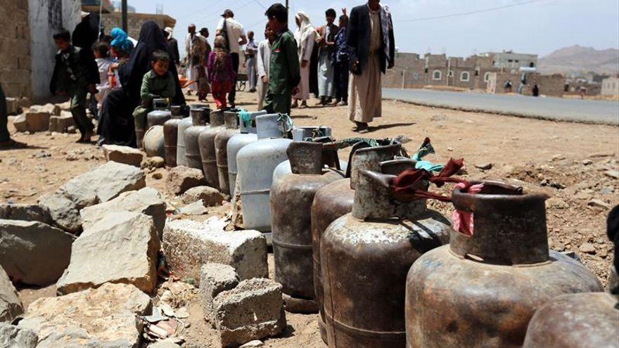 Yemeníes junto a contenedores de gas vacíos esperando al suministro en una gasolinera en Saná.