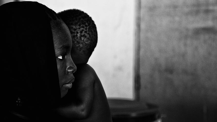 Una madre con su hijo en brazos espera su turno en el centro de recuperación infantil nutricional de Virimadjo en Bamako (centro referencial, para la recuperación de niños desnutridos) de la comuna 6 de Bamako, la más pobre de la capital Maliense. | ÁNGEL COLINA (17/04/2014)