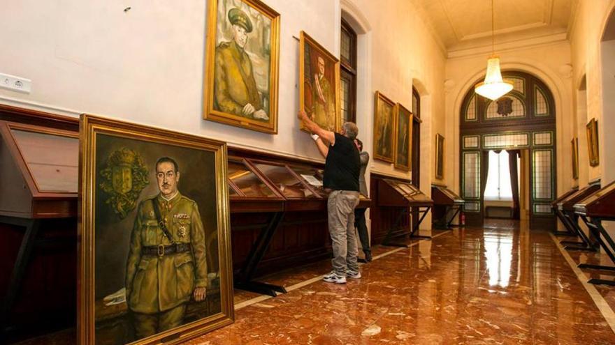 Operarios del Ayuntamiento de A Coruña este lunes retirando retratos de militares franquistas que fueron nombrados alcaldes