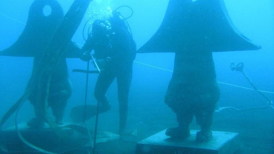 En la imagen, dos figuras de los 'Enanos subacuáticos' en el lecho marino, con uno de los buzos que han participado en hundimiento. Foto. DANNY MEDINA