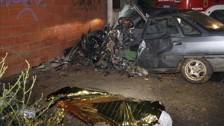 Un coche con la frontal destrozada. En primer término el cuerpo sin vida del conductor. /EFE