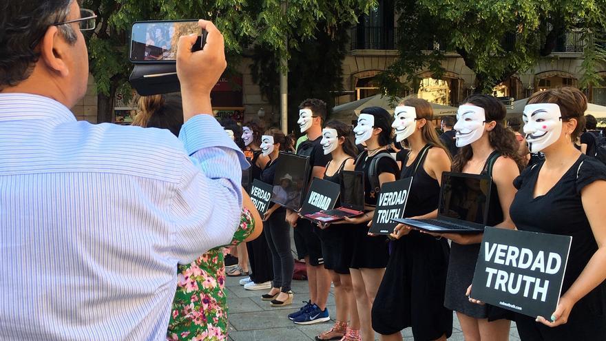 Un ciudadano fotografía a los activistas del 'cubo de la verdad' en Barcelona