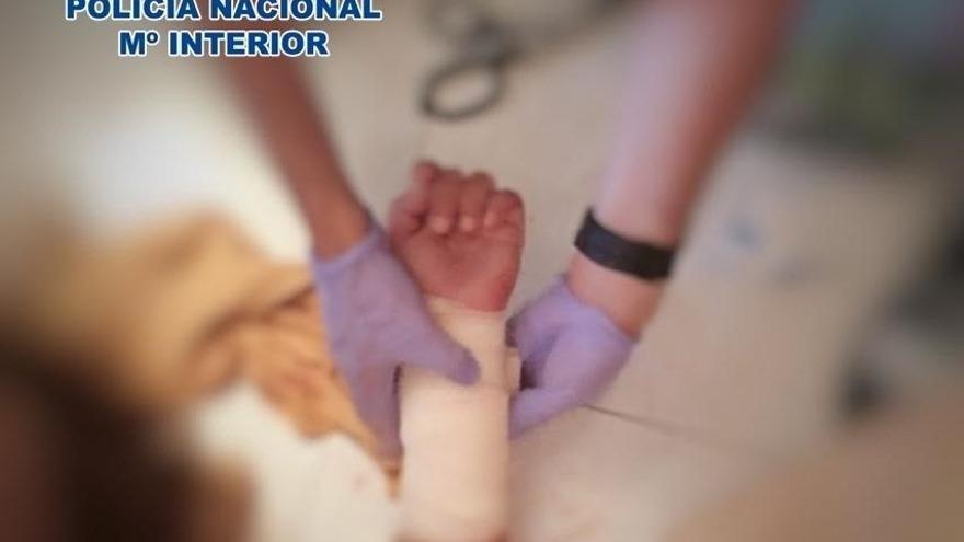 Los agentes, realizando las maniobras de primeros auxilios a la mujer