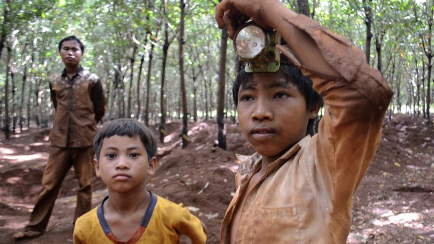Nhun y Bu, hermanos de 13 y 10 años, trabajan en la mina artesanal de gemas limpiando las zonas más estrechas de los pozos / Carlos Hernández