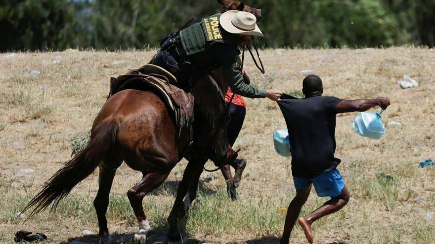 Un agente de la patrulla fronteriza estadounidense agarra la camisa de un migrante que intenta regresar a Estados Unidos por el río Grande.