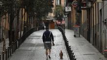 Un hombre pase a su perro en el madrileño barrio de Malasaña.