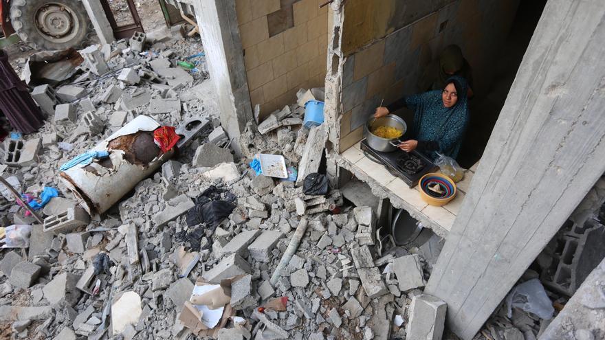 Una mujer cocina en su casa destruida tras la ofensiva sobre Gaza. 2021