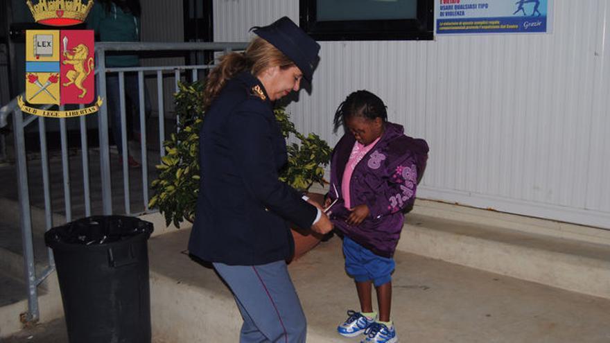 Oumoh, de cuatro años, siendo atendida por una agente de policía italiana