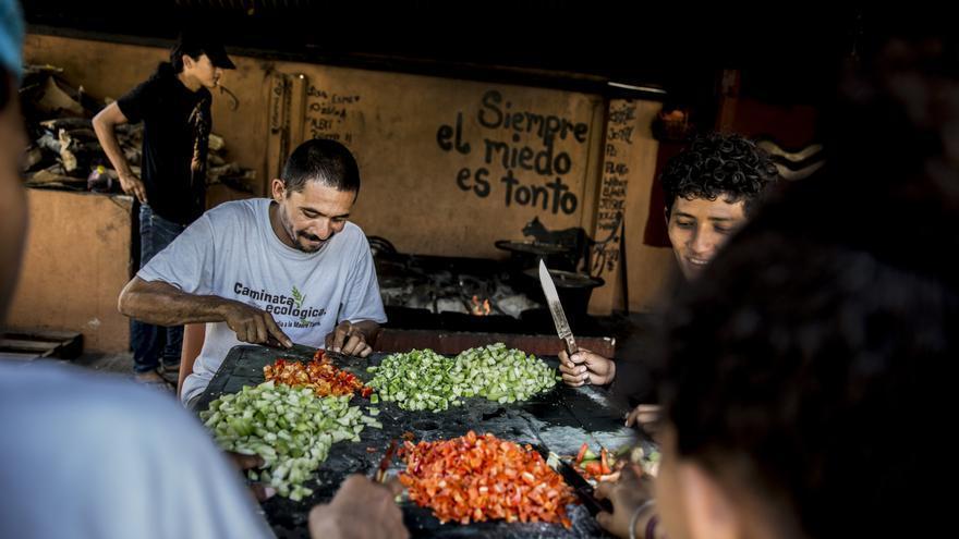 Los migrantes colaboran en las tareas de preparación de las comidas en el albergue de La 72.