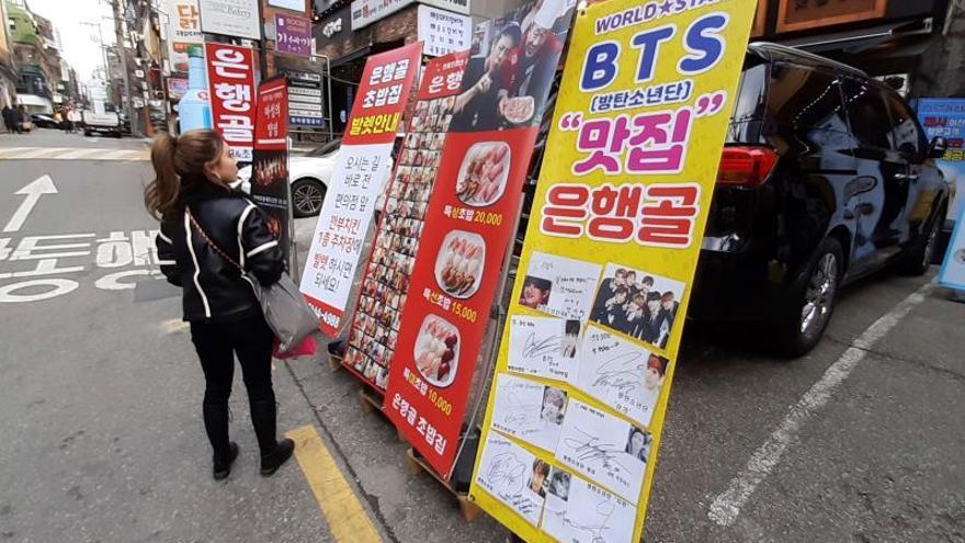 """Una viandante se detiene a leer carteles publicitarios de restaurantes junto a fotos y autógrafos (dcha) de diferentes estrellas del """"Hallyu"""" en la zona de Garosugil, el lunes 20, en Seúl (Corea del Sur). De tiendas de K-Pop a escenarios de K-Dramas, Seúl alberga infinitos espacios ligados a la industria del entretenimiento deCoreadelSury es el destino soñado de cualquier fan del """"Hallyu"""", la oleada de cultura popular de este país que ha barrido el planeta."""