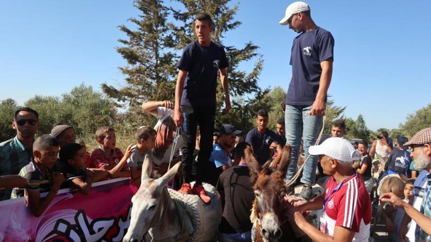 Vecinos marroquíes al inicio de la carrera de borricos que tuvo lugar en la localidad de Beni Ammar, en el marco de la 12º Edición del Festival del Burro, con el que quiere reivindicar el valor de este animal, tan denostado en la cultura popular marroquí, al que además se le ha sumado un inédito concurso de belleza de los asnos locales.