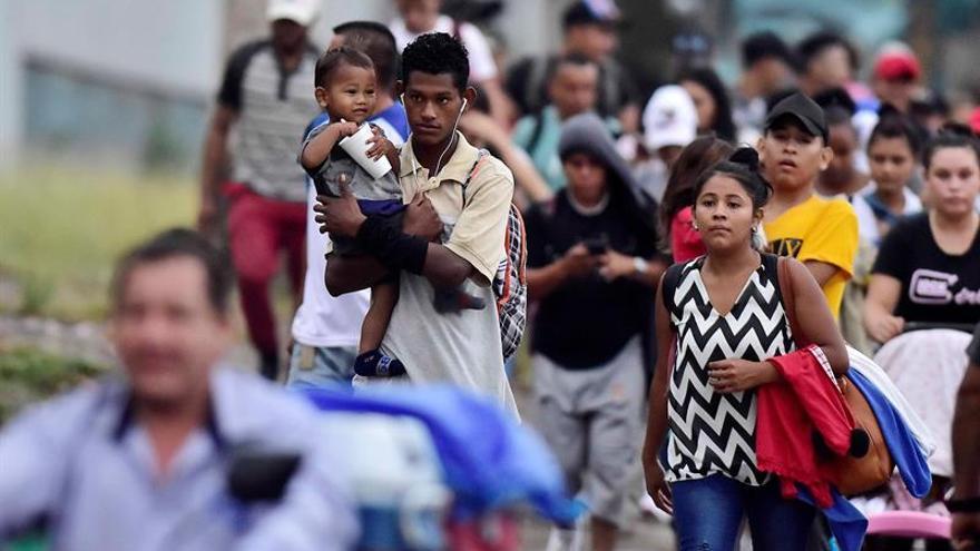 Un padre que carga a su hijo fue registrado este miércoles al caminar en medio de una caravana migrante, rumbo a la frontera guatemalteca de Agua Caliente, a su paso por San Pedro Sula (Honduras).
