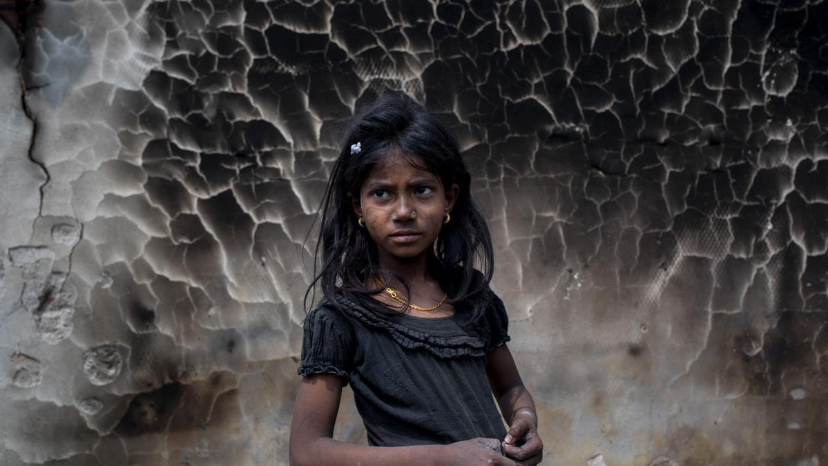Una niña refugiada rohinyá frente a un muro quemado tras el gran incendio que se produjo hace dos días en el campo de refugiados de Balukhali, en Cox's Bazar.