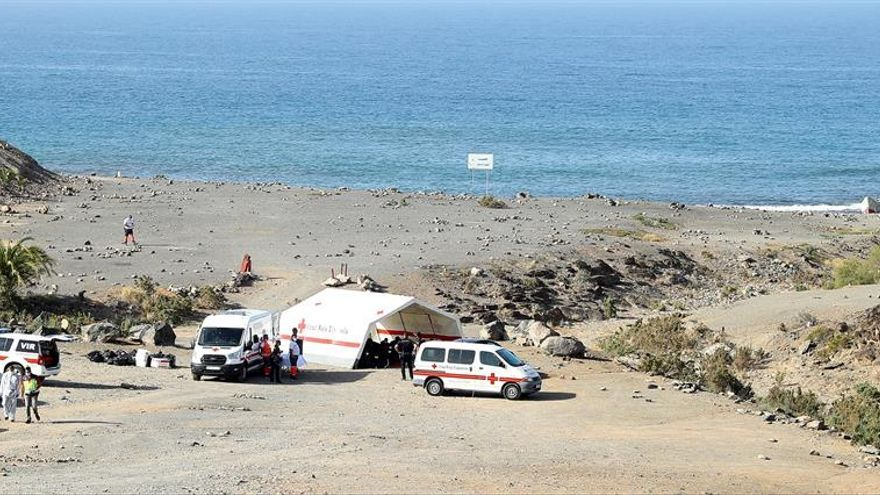 Los inmigrantes en la carpa que Cruz Roja instaló en la misma playa para atenderlos y la barquilla en la que llegaron a la derecha.