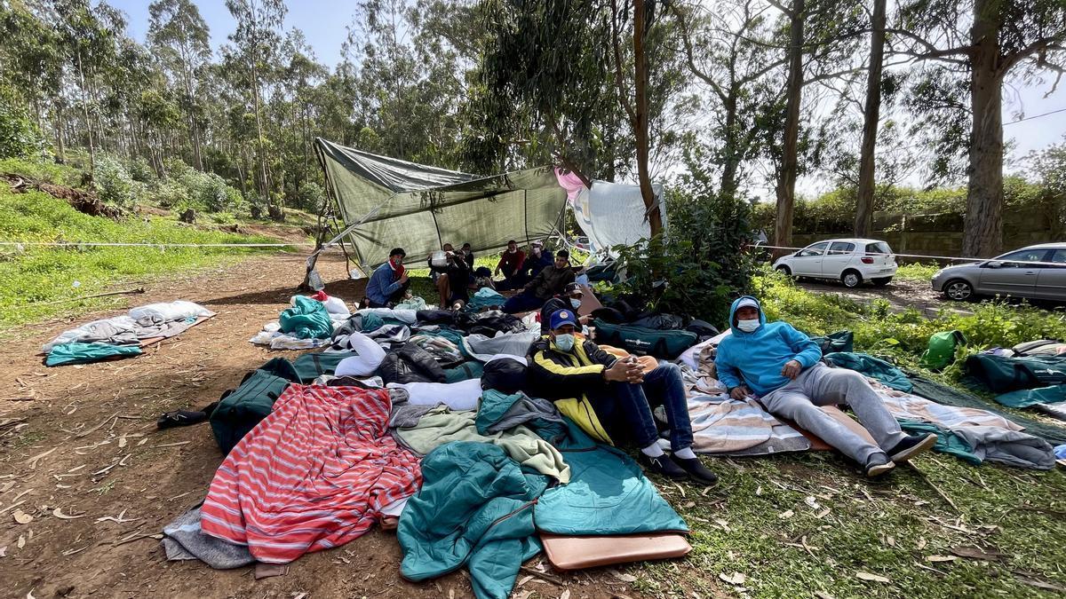 Un grupo de hombres acampa en el exterior del campamento para migrantes de Las Raíces para exigir una solución