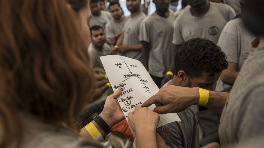 La tripulación del Open Arms organiza en grupos a los migrantes rescatados.