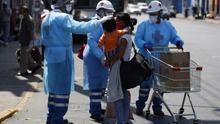 Personal de la Cruz Roja asiste a cientos de personas que esperan junto a una terminal de buses en Lima con la esperanza de poder regresar a sus lugares de origen.