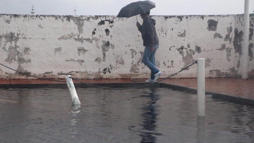 Un vecino de Santa Cruz de La Palma se protege de la lluvia  con un paraguas, este martes. Foto:  SIXTO SANTOS.
