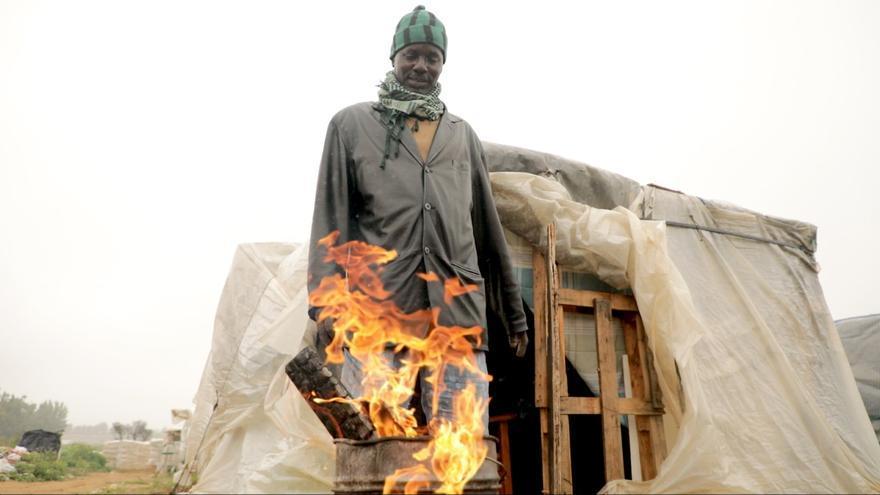 Birnaka frente a su chabola prepara el fuego para calentarse y hervir el agua que le servirá para el aseo.