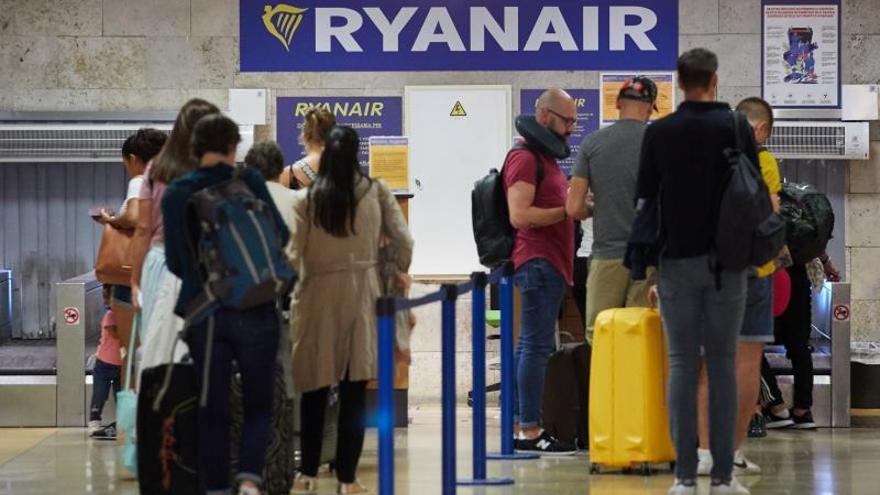 Varios viajeros esperan en los mostradores de facturación de la compañía aérea Ryanair.